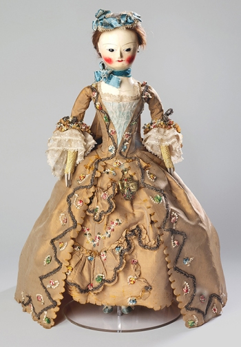 Fashion doll with costume and accessories, 1755–60; wood, gesso, paint, glass, human hair, knitted cotton, satin, silk, gilt braid, wire, silk gauze, linen, cotton, and silk satin, 60 x 42 x 43 cm (London: V&A Museum)